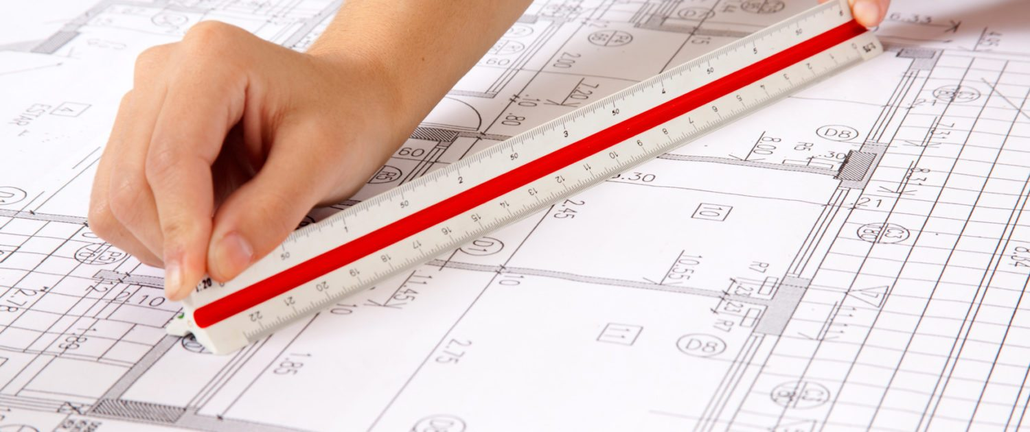 scale ruler on a set of blueprints construction company